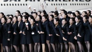 Nowo zatrudnione stewardessy linii lotniczych Japan Airlines pozują do zdjęcia na tle samolotu w barwach linii na lotnisku Haneda w Tokio. Stopa bezrobocia w Japonii spadła w październiku 2013 roku do 4 proc. Na początku roku wynosiła 4,2 proc. Fot. Kiyoshi Ota, Bloombergs Best Photos 2013.