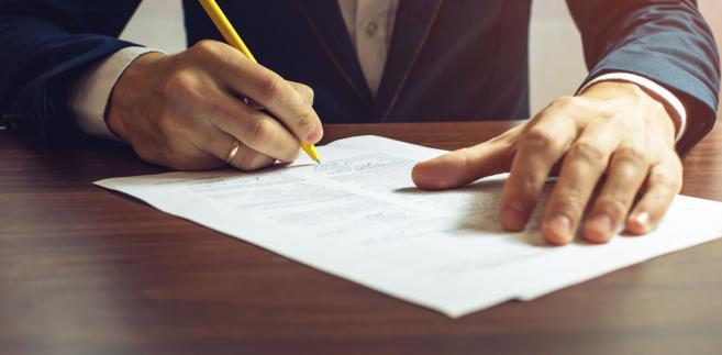 Mężczyzna podpisuje dokumenty