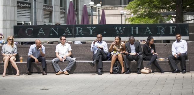 Pracownicy w biurowej dzielnicy Canary Wharf w Londynie jedzą lunch na świeżym powietrzu.